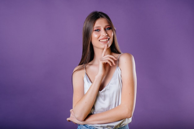 Una giovane bella ragazza mostra emozioni e sorrisi su uno spazio viola. ragazze per la pubblicità.