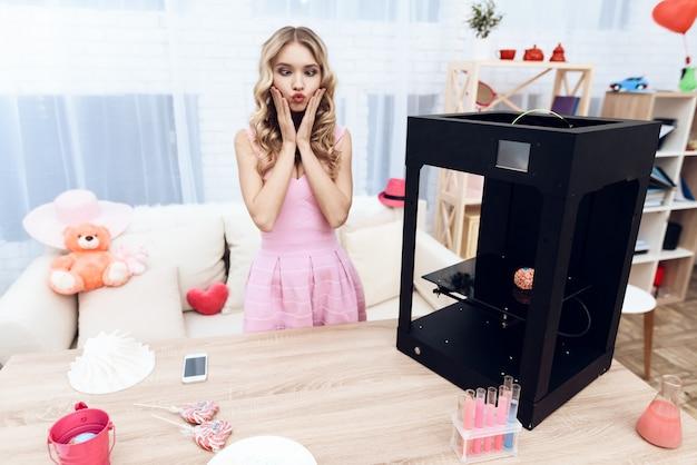 Una giovane bella ragazza sta sperimentando con una stampante 3d.