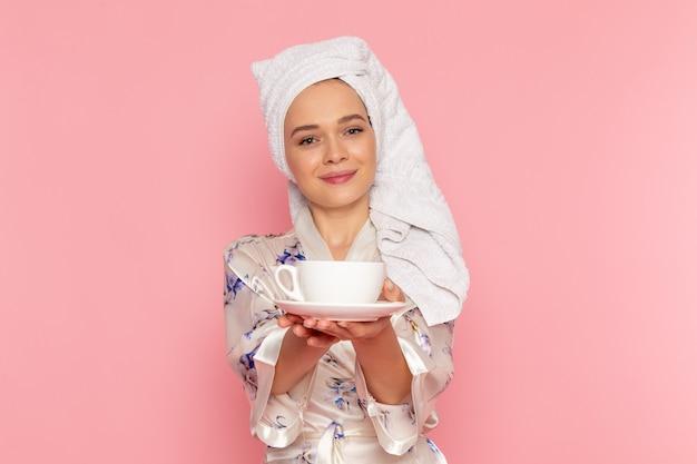 Una giovane bella signora di vista frontale in accappatoio che tiene tazza di caffè mentre sorridendo