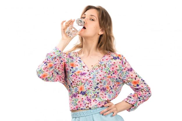 Una giovane bella signora di vista frontale in camicia colorata fiore progettato e gonna blu che beve acqua sul bianco