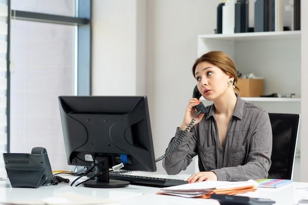 Una giovane bella signora di vista frontale in camicia grigia che lavora al suo pc che si siede dentro il suo ufficio che parla sul telefono della città durante l'attività di lavoro di costruzione di giorno
