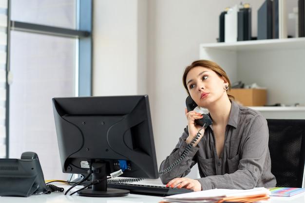 Una giovane bella signora di vista frontale in camicia grigia che lavora al suo pc che si siede dentro il suo ufficio che parla sul telefono durante l'attività di lavoro di costruzione di giorno