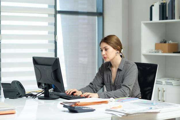 Una giovane bella signora di vista frontale in camicia grigia che lavora al suo pc che si siede dentro il suo ufficio durante l'attività di lavoro di costruzione di giorno