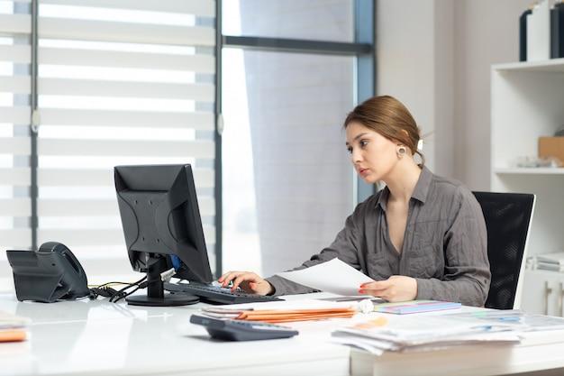 Una giovane bella signora di vista frontale in camicia grigia che lavora al suo pc e che guarda attraverso i documenti che si siedono dentro il suo ufficio durante l'attività di lavoro di costruzione di giorno