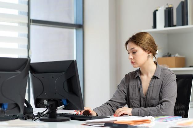 Una giovane bella signora di vista frontale in camicia grigia che lavora con i documenti facendo uso del suo pc che si siede dentro il suo ufficio durante l'attività di lavoro di costruzione di giorno