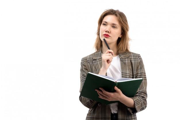 Una giovane bella signora di vista frontale in jeans e cappotto neri della maglietta bianca che tengono libro verde che annota pensando sul bianco