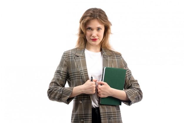 Una giovane bella signora di vista frontale in jeans e cappotto neri della maglietta bianca che tengono libro verde e penna sul bianco