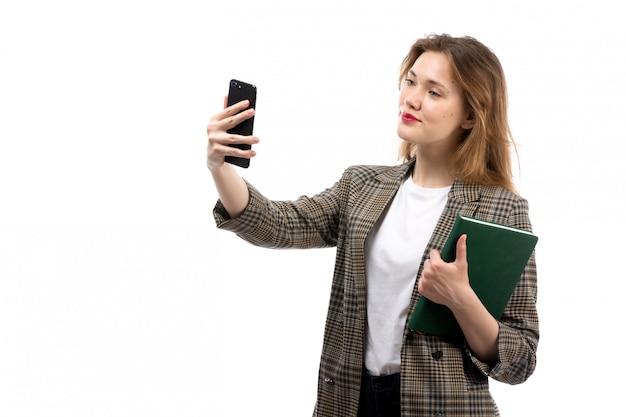 Una giovane bella signora di vista frontale in jeans neri e cappotto della maglietta bianca che tengono smartphone nero che prende un selfie e un libro verde sul bianco