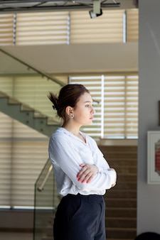Una giovane bella signora di vista frontale in pantaloni neri della camicia bianca che esaminano la distanza che posa nella sala che aspetta durante l'attività di lavoro della costruzione di giorno