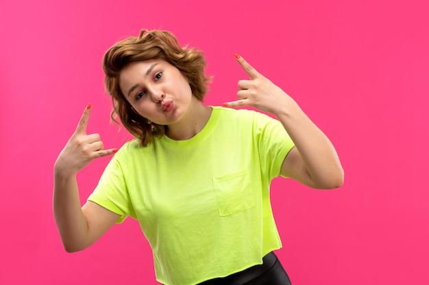Una giovane bella signora di vista frontale nella posa dei pantaloni del nero della camicia colorata acido