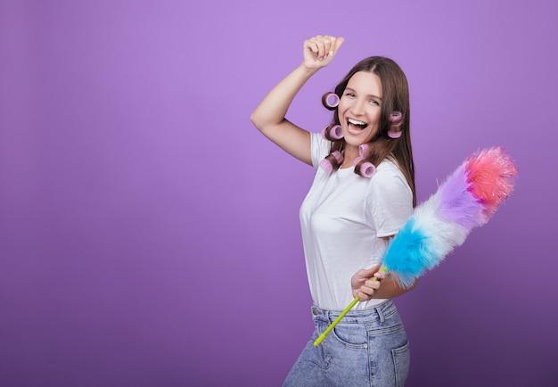 Una giovane bellezza in bigodini canta canzoni e balla mentre pulisce.
