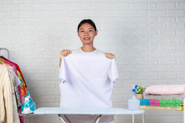 Una giovane cameriera che sta preparando una camicia sul suo asse da stiro con un mattone bianco.
