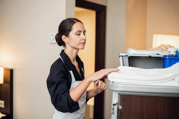 Una giovane cameriera in uniforme che ottiene degli asciugamani freschi