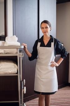 Una giovane cameriera in uniforme felice che trasporta gli asciugamani
