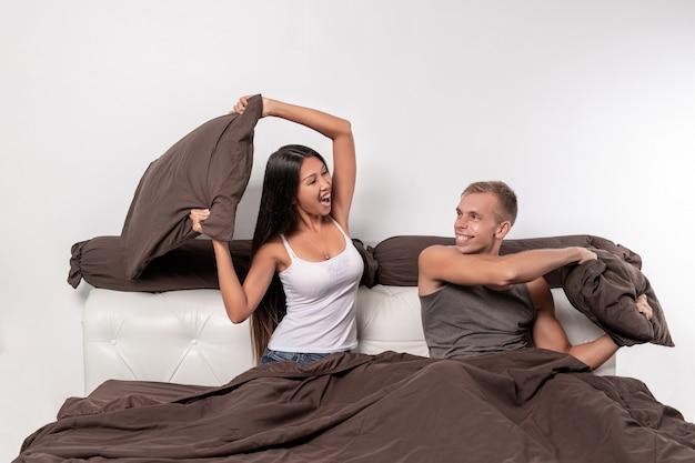 Una giovane coppia allegra di un ragazzo e una ragazza hanno deciso di organizzare una lotta con i cuscini nel loro letto