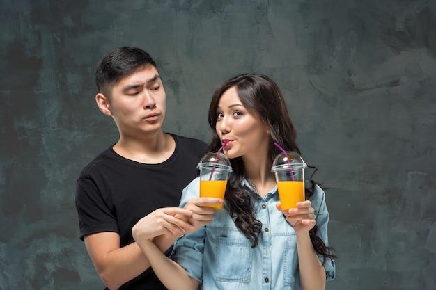 Una giovane coppia asiatica con un bicchiere di succo d'arancia