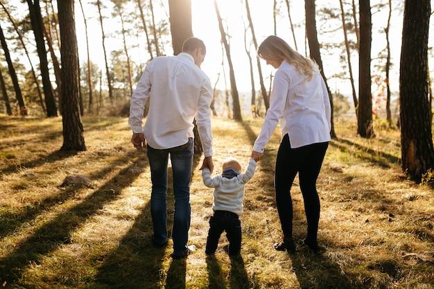 Una giovane coppia cammina nei boschi con un ragazzino