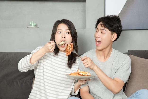 Una giovane coppia cinese stava mangiando sul divano.