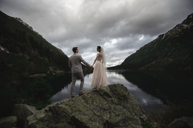 Una giovane coppia di sposi gode di una vista sulle montagne sulla riva di un lago morskie oko