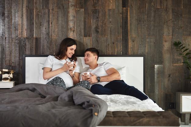 Una giovane coppia di sposi in attesa di un bambino. belle coppie che giacciono in camera da letto fanno piani per la nascita di un bambino. primo figlio, dopo il parto, giovane famiglia.