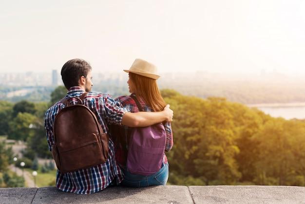 Una giovane coppia di turisti è seduta sul parapetto.