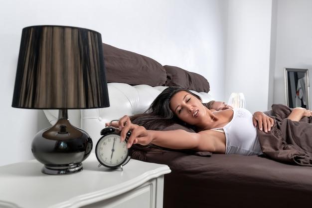 Una giovane coppia di un ragazzo e una ragazza dormono sdraiati nel letto, ma la loro sveglia suona
