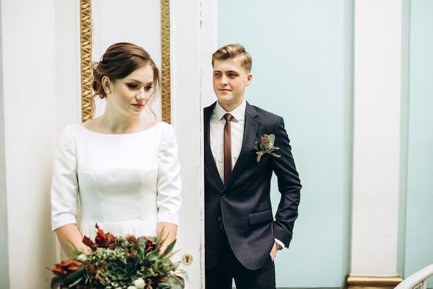 Una giovane coppia in abiti da sposa in un antico palazzo.