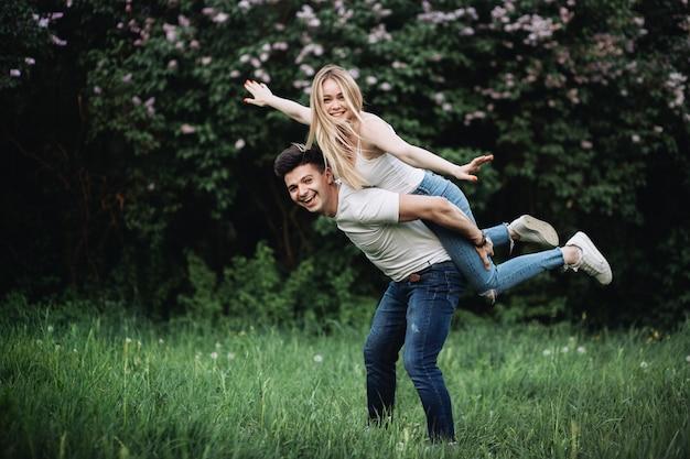 Una giovane coppia innamorata si diverte e scherza di fronte a un cespuglio fiorito