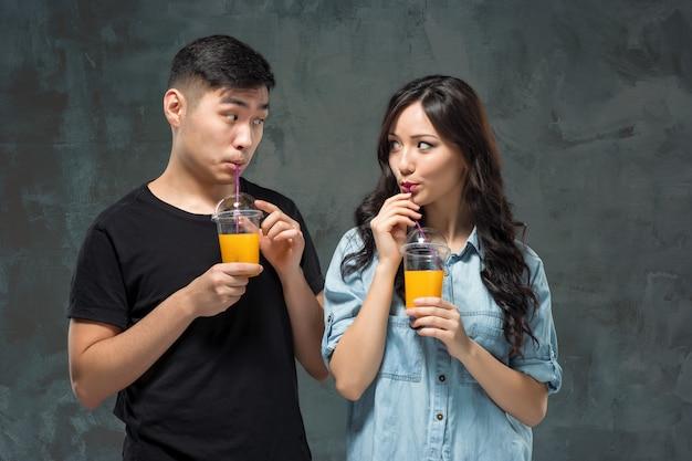 Una giovane coppia piuttosto asiatica con un bicchiere di succo d'arancia