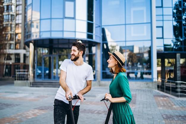 Una giovane coppia romantica con scooter elettrici in una data, camminando in città.