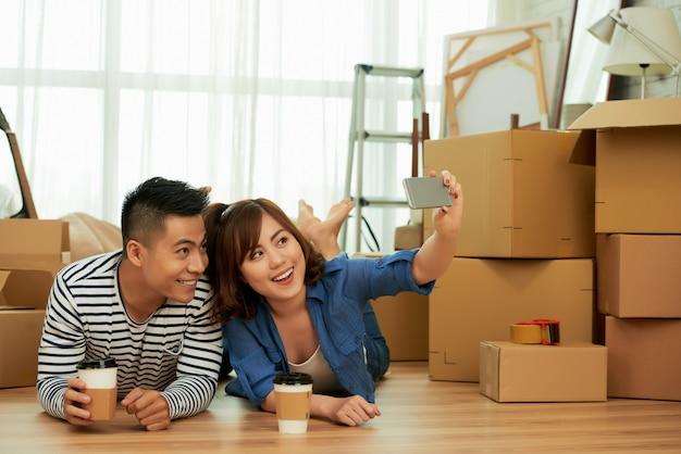 Una giovane coppia sdraiata spensierata sul pavimento prendendo selfie davanti a scatole di imballaggio