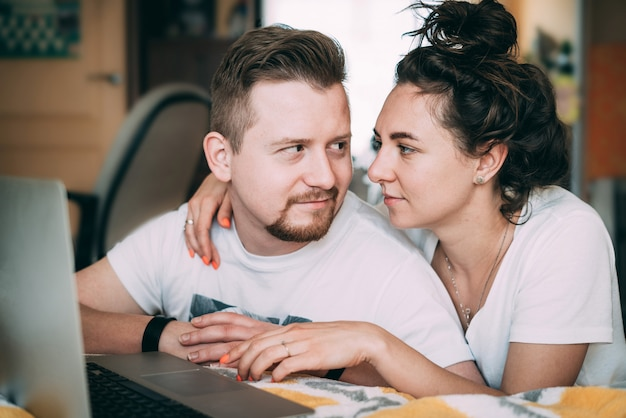Una giovane coppia si siede a casa e fa acquisti online. acquisti online.