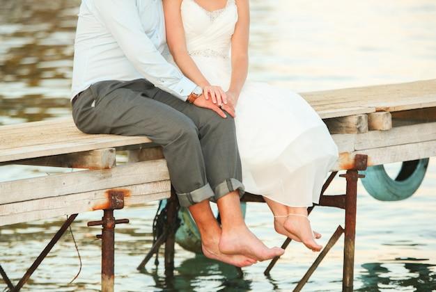Una giovane coppia si tiene per mano e si siede su un ponte sul fiume