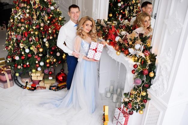 Una giovane coppia-un uomo e una donna in abiti eleganti con un regalo in mano, albero di natale e decorazioni