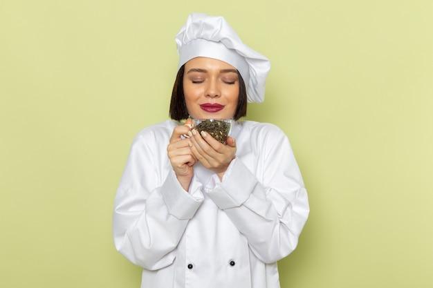 Una giovane cuoca femminile di vista frontale in vestito bianco del cuoco e tazza della tenuta del cappuccio con tè secco sulla parete verde