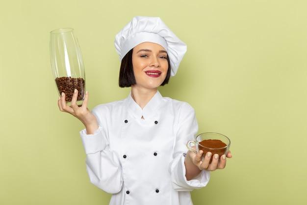 Una giovane cuoca femminile di vista frontale in vestito bianco del cuoco e vaso della tenuta del cappuccio con i semi di caffè sul colore dell'alimento del lavoro della signora della parete verde