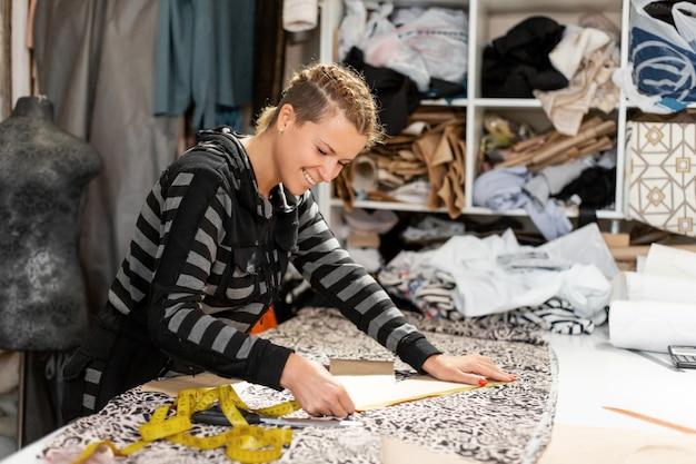 Una giovane designer di abiti. misure per centimetro di taglio sul tessuto per realizzare abiti. fare vestiti su ordinazione, concetto di stilista