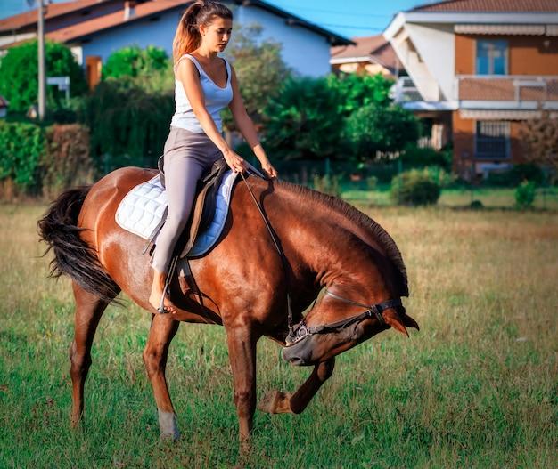 Una giovane donna a cavallo nei campi