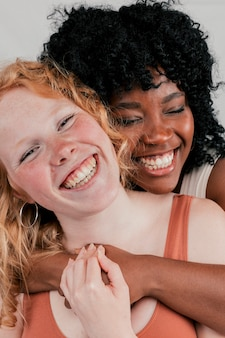 Una giovane donna africana che abbraccia il suo amico dalla pelle chiara