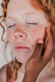 Una giovane donna africana che tocca la guancia del suo amico caucasico