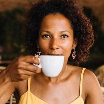 Una giovane donna afro-americana che beve caffè