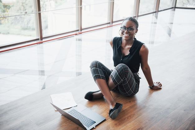 Una giovane donna afroamericana è felice con un computer portatile.