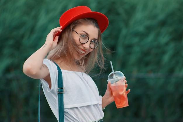 Una giovane donna alla moda con un drink rinfrescante mentre si cammina