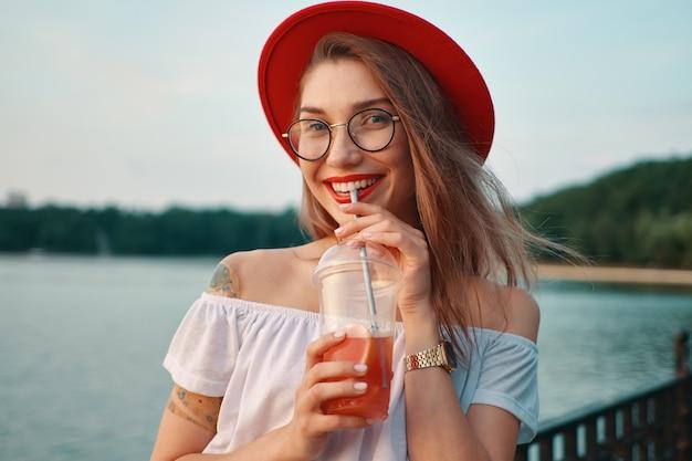 Una giovane donna alla moda con un drink rinfrescante mentre sorridente