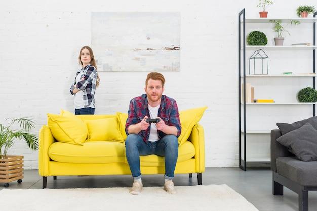 Una giovane donna arrabbiata in piedi dietro il divano giallo con il suo fidanzato a giocare al videogioco