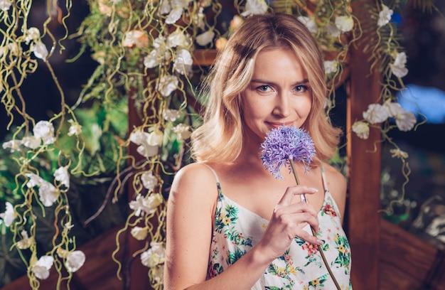 Una giovane donna attraente che tiene il fiore viola dell'allium a disposizione