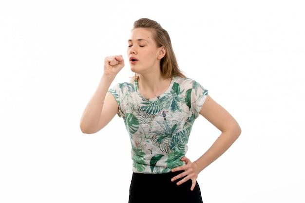 Una giovane donna attraente di vista frontale in camicia progettata e gonna nera che tossiscono sul bianco