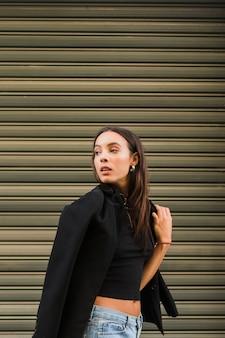 Una giovane donna attraente in piedi davanti all'otturatore di ferro guardando oltre la spalla