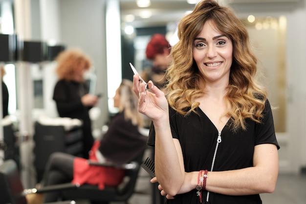 Una giovane donna attraente nel suo salone di bellezza con i clienti dietro di lei