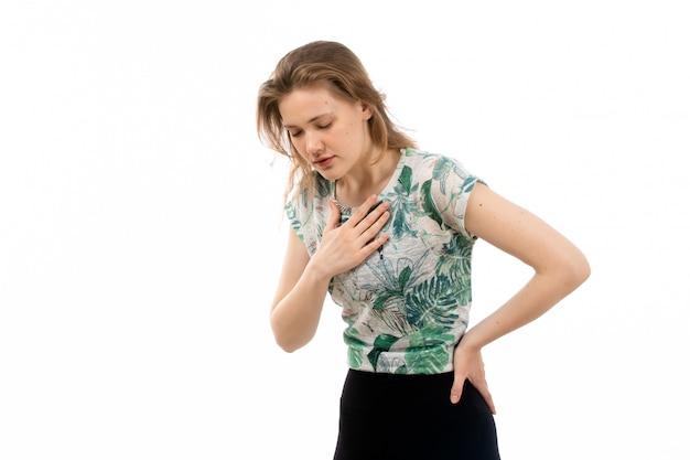 Una giovane donna attraente vista frontale in camicia progettata e pantaloni neri che soffrono di problemi di respiro sul bianco